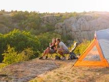 Homme et femme mangeant sur un fond naturel Un couple appréciant la belle vue Campant, concept de déplacement Copiez l'espace Photographie stock libre de droits