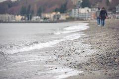 Homme et femme marchant à une distance le long du rivage Images stock