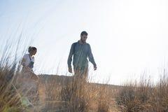 Homme et femme marchant dans la longue herbe Photo libre de droits