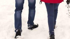 Homme et femme marchant dans la neige, pieds en gros plan banque de vidéos