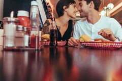 Homme et femme partageant des pommes frites se reposant à un restaurant image stock