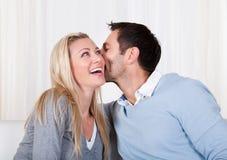 Homme et femme partageant un secret Photographie stock libre de droits