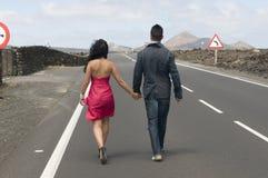 Homme et femme partant sur la route Photographie stock libre de droits
