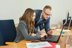 Homme et femme passant le temps dans le bureau Femme s'asseyant derrière Images stock