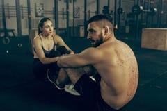 Homme et femme pendant les exercices dans le gymnase de forme physique Crossfit image stock
