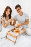 Homme et femme prenant le petit déjeuner dans le lit Images libres de droits