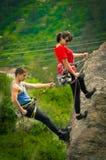 Homme et femme rapelling en bas de la montagne Images libres de droits