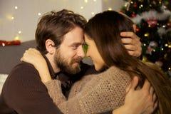 Homme et femme regardant dans l'un l'autre des yeux en plan rapproché de nuit de Noël d'amour Photographie stock libre de droits