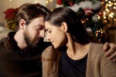 Homme et femme regardant dans l'un l'autre des yeux dans le tir moyen de nuit de Noël d'amour Photo libre de droits