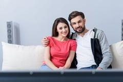 Homme et femme regardant la TV sur le divan Photo libre de droits