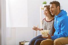 Homme et femme regardant la TV sur le divan images stock