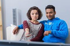 Homme et femme regardant la TV sur le divan image libre de droits