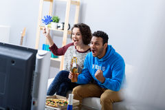 Homme et femme regardant la TV sur le divan photographie stock