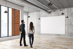 Homme et femme regardant le panneau d'affichage Photographie stock libre de droits