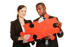 Homme et femme reliant des morceaux de puzzle denteux Image libre de droits