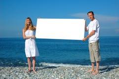 Homme et femme retenant le panneau-réclame blanc Images stock