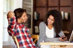 Homme et femme s'asseyant à la table avec l'ordinateur portable et le téléphone portable Photographie stock