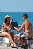 Homme et femme s'asseyant à la table sous le ciel ouvert Photographie stock libre de droits