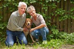 Homme et femme s'asseyant avec le chien dans un jardin Photographie stock libre de droits
