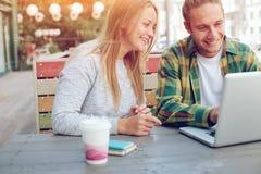 Homme et femme s'asseyant dans le couple de café de rue, gai et de sourire Images stock
