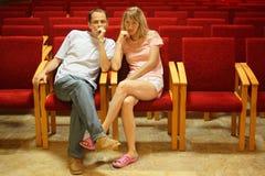 Homme et femme s'asseyant dans le hall vide de présentation. Photographie stock libre de droits