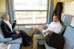 Homme et femme s'asseyant dans parler de train Images stock