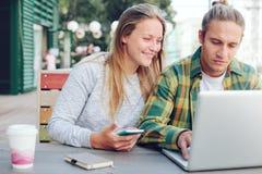 Homme et femme s'asseyant en café de rue avec l'ordinateur portable et le téléphone portable, couple gai Photos libres de droits