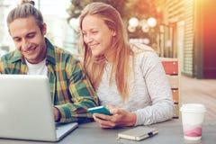 Homme et femme s'asseyant en café de rue avec le couple d'ordinateur portable, gai et de sourire Photo stock