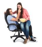 Homme et femme s'asseyant ensemble dans le fauteuil mangeant du maïs de bruit Photo libre de droits