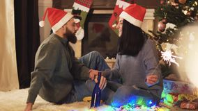 Homme et femme s'asseyant près de l'arbre de Noël, femme tenant des cierges magiques à disposition Brûlures de cierge magique dan banque de vidéos