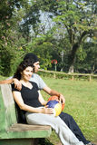 Homme et femme s'asseyant sur un banc de stationnement - verticale Photographie stock libre de droits