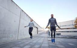Homme et femme s'exerçant avec la saut-corde dehors Photographie stock