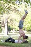 Homme et femme s'exerçant en parc, ils exécutent des acrobaties Photos stock