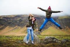 Homme et femme sautants en vallée de l'Islande Image libre de droits