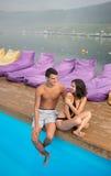 Homme et femme se reposant au bord de la piscine dans la station de vacances sur le fond de belles vues des forêts, collines Photos stock