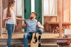Homme et femme se reposant sur le porche, homme jouant sur la guitare Image libre de droits
