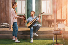 Homme et femme se reposant sur le porche, homme jouant sur la guitare Image stock
