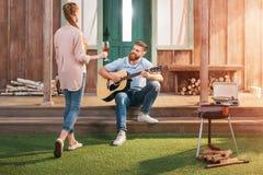 Homme et femme se reposant sur le porche, homme jouant sur la guitare Images libres de droits