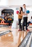 Homme et femme se tenant avec des boules de bowling dans le club Photo stock