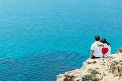 Homme et femme situant ensemble dans l'amour avec la forme de coeur sur le leur des t-shorts Images libres de droits