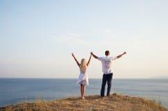 Homme et femme soulevant leurs mains au ciel Images stock