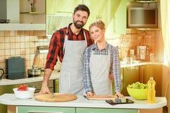 Homme et femme souriant, cuisine Photos stock