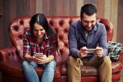 Homme et femme souriants à l'aide des smartphones Photographie stock libre de droits
