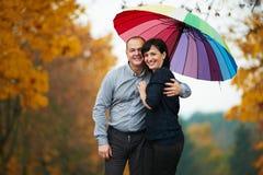 Homme et femme sous le parapluie coloré lumineux Photo stock