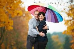 Homme et femme sous le parapluie coloré lumineux Photographie stock