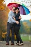 Homme et femme sous le parapluie coloré lumineux Images stock