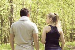 Homme et femme sportifs après exercice de forme physique Vue du dos dans la forêt Images stock