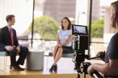 Homme et femme sur l'ensemble pour une entrevue de TV, foyer sur le premier plan Photographie stock libre de droits