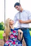 Homme et femme sur l'oscillation en parc, couple dans l'amour Photographie stock