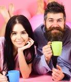 Homme et femme sur la configuration de sourire de visages, fond rose Couples en café de boissons d'amour dans le lit Homme et fem Images stock